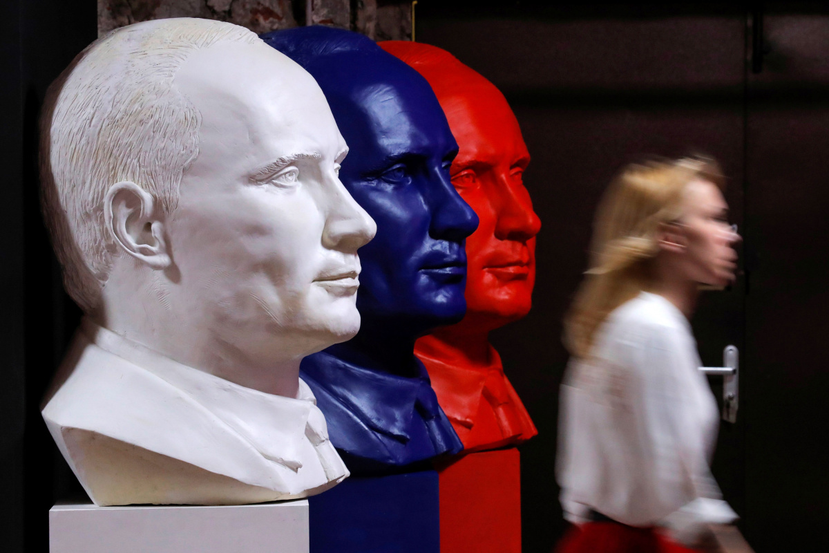 """A woman walks past busts depicting Russian president Vladimir Putin in the colours of the Russian national flag at the """"SUPERPUTIN"""" exhibition in UMAM museum in Moscow"""