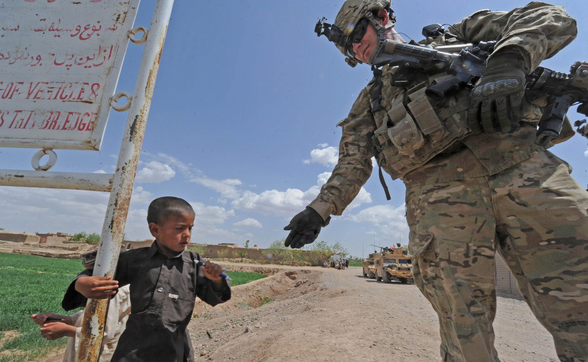 A coalition Special Operations Forces soldier gives a pen to a young child in Sanawghan village, Herat Province, Afghanistan. Flickr/Department of Defense