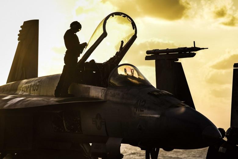 Sailors prepare an F/A-18E Super Hornet for flight operations on the flight deck of the aircraft carrier USS Dwight D. Eisenhower. Flickr/U.S. Navy