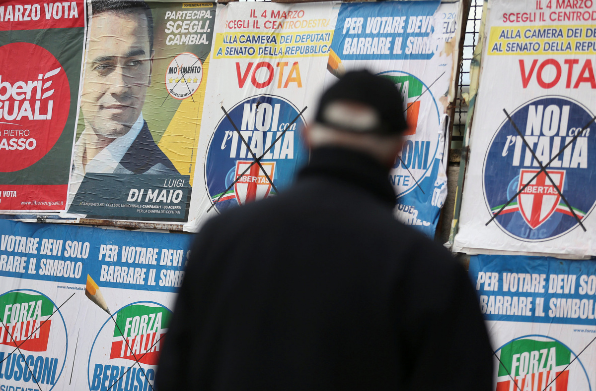 A man stands to look electoral posters in Pomigliano D'Arco, near Naples, Italy, February 21, 2018. Picture taken February 21, 2018. REUTERS/Alessandro Bianchi