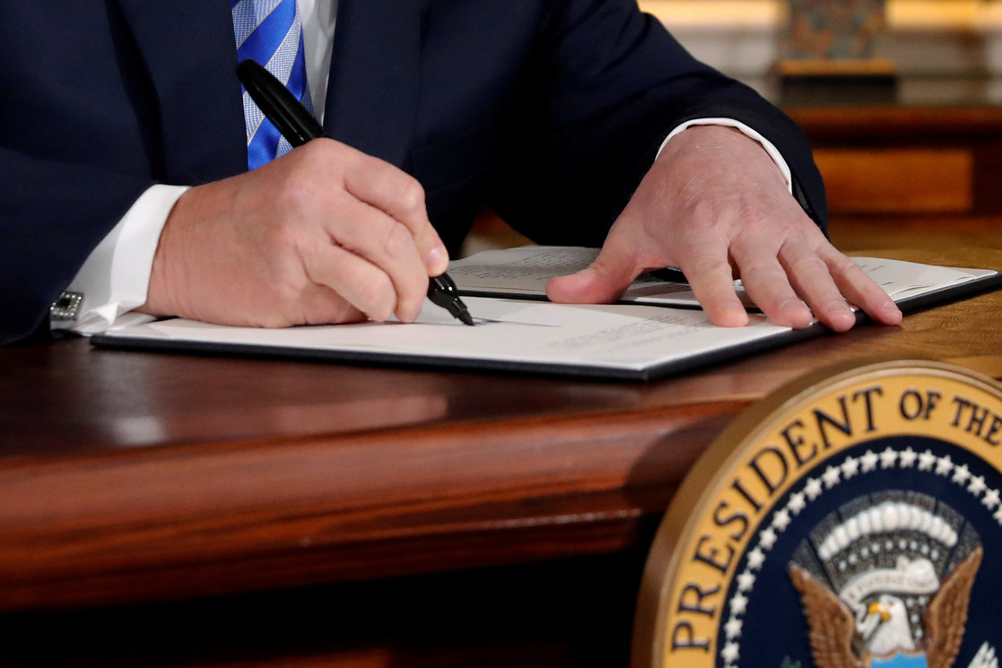 U.S. President Donald Trump signs a proclamation declaring his intention to withdraw from the JCPOA Iran nuclear agreement in the Diplomatic Room at the White House in Washington, U.S. May 8, 2018. REUTERS/Jonathan Ernst/File Photo