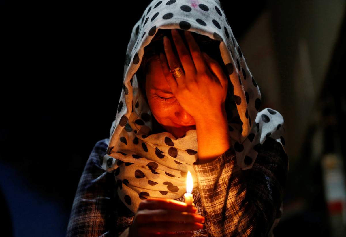 A woman cries as she holds a lit candle for the victims of Wednesday's blast in Kabul, Afghanistan June 1, 2017. REUTERS/Mohammad Ismail