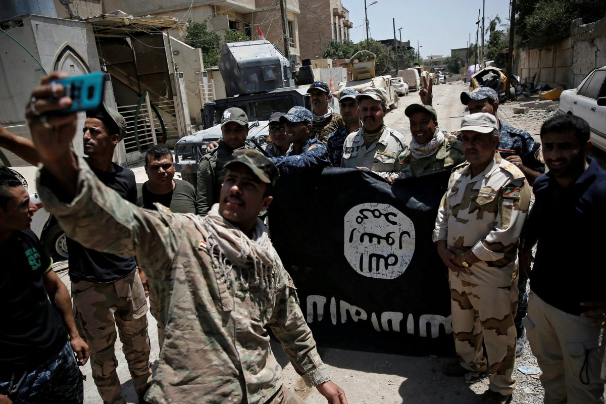 Members of the Iraqi Army's 9th Armoured Division are photographed with an Islamic State flag, claimed after fighting with Islamic State militants in western Mosul, Iraq June 17, 2017. REUTERS/Alkis Konstantinidis/File Photo