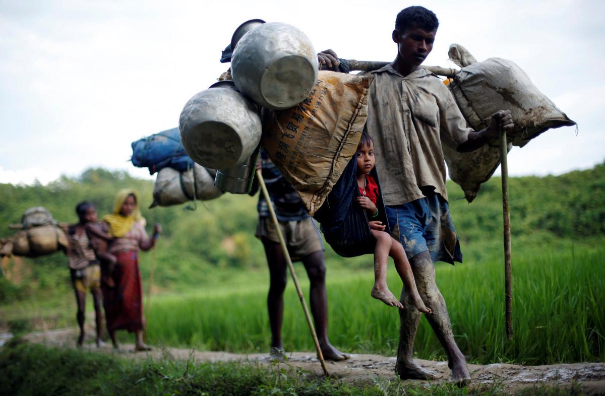 Rohingya refugees walk through a paddy field after crossing the Bangladesh-Myanmar border in Cox's Bazar, Bangladesh September 8, 2017. REUTERS/Danish Siddiqui