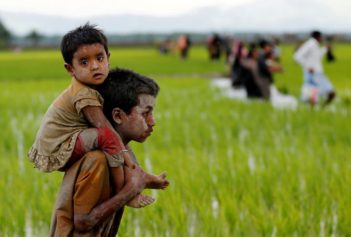 A Rohingya boy carries a child after after crossing the Bangladesh-Myanmar border in Teknaf, Bangladesh, September 1, 2017. REUTERS/Mohammad Ponir Hossain​