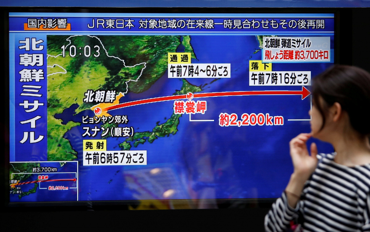 A passerby looks at a TV screen reporting news about North Korea's missile launch in Tokyo, Japan September 15, 2017.