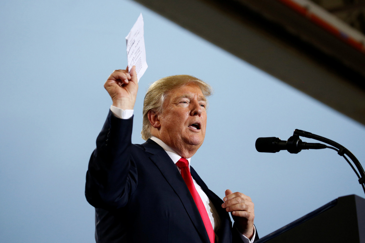 U.S. President Donald Trump holds up a list of politicians as he speaks about tax reform in Harrisburg, Pennsylvania, U.S., October 11, 2017. REUTERS/Joshua Roberts