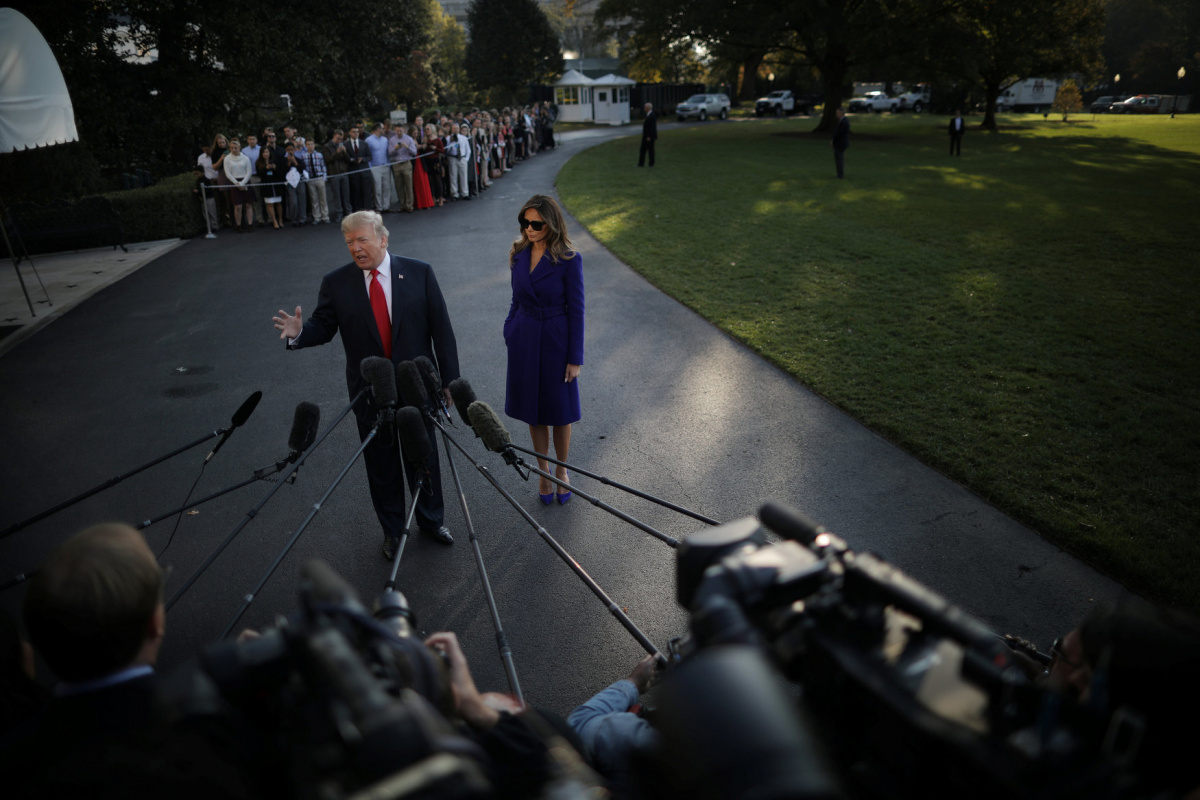 U.S. President Donald Trump talks with reporters accompanied by First Lady Melania Trump as they depart the White House for a trip to Asia, in Washington D.C., U.S. November 3, 2017. REUTERS/Carlos Barria