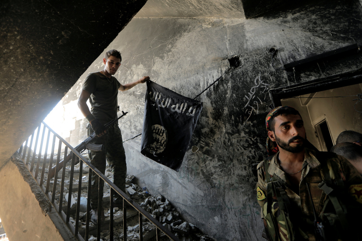 "A member of the Syrian Democratic Forces calls his comrades during the fighting with Islamic State fighters in Raqqa, Syria, August 14, 2017. Zohra Bensemra: ""The Reuters team waited almost all day behind Syrian Democratic Forces members who were fighting Islamic State in Raqqa to lead us into this building. They had posted themselves there temporarily. They took it after fierce fighting. It was just at very short distance from the Islamic State's position. Whenever a building or a district was taken from t"