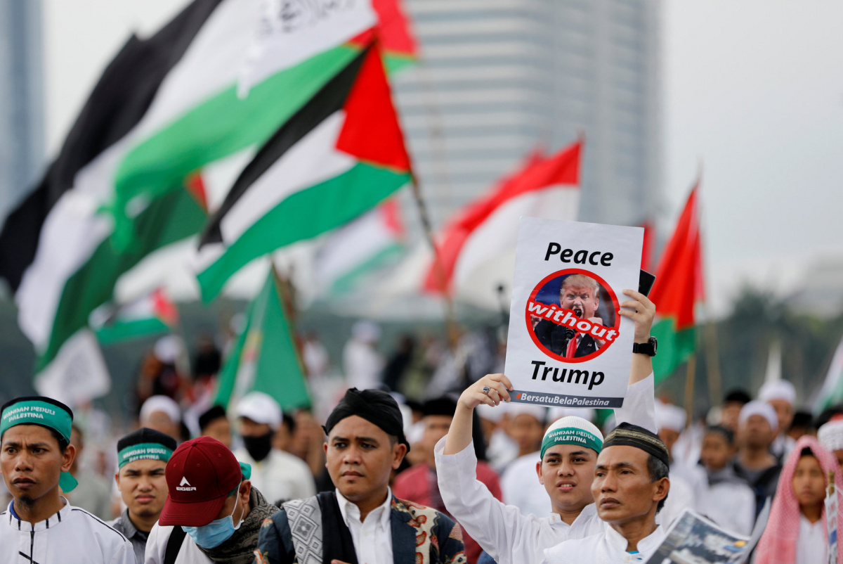 A protester holds a sign during a rally to condemn U.S. President Donald Trumps's decision to recognise Jerusalem as Israel's capital, at Monas, the national monument, in Jakarta, Indonesia, December 17, 2017. REUTERS/Darren Whiteside
