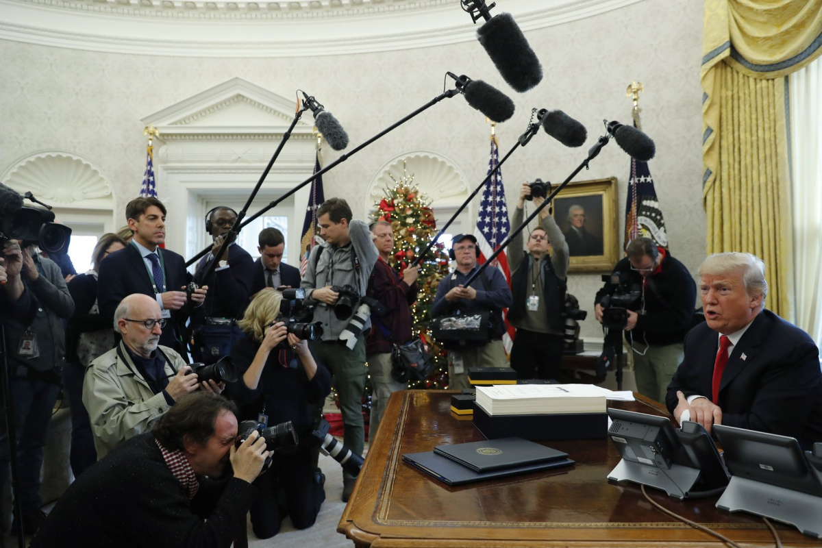 U.S. President Donald Trump sits at his desk while signing the $1.5 trillion tax overhaul plan along with a short-term government spending bill in the Oval Office of the White House in Washington, U.S., December 22, 2017. REUTERS/Jonathan Ernst