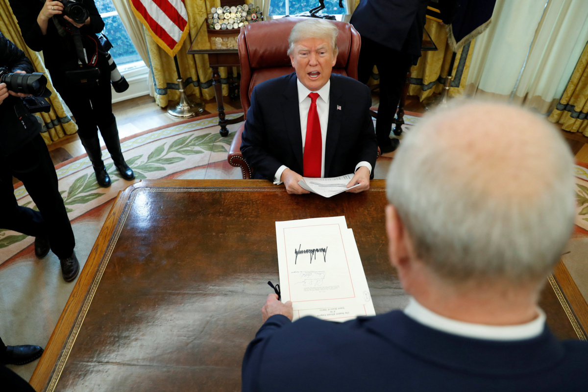 White House Chief of Staff John Kelly stands over U.S. President Donald Trump's desk as reporters exit after he signed sweeping tax overhaul legislation into law in the Oval Office at the White House in Washington, U.S. December 22, 2017. REUTERS/Jonathan Ernst