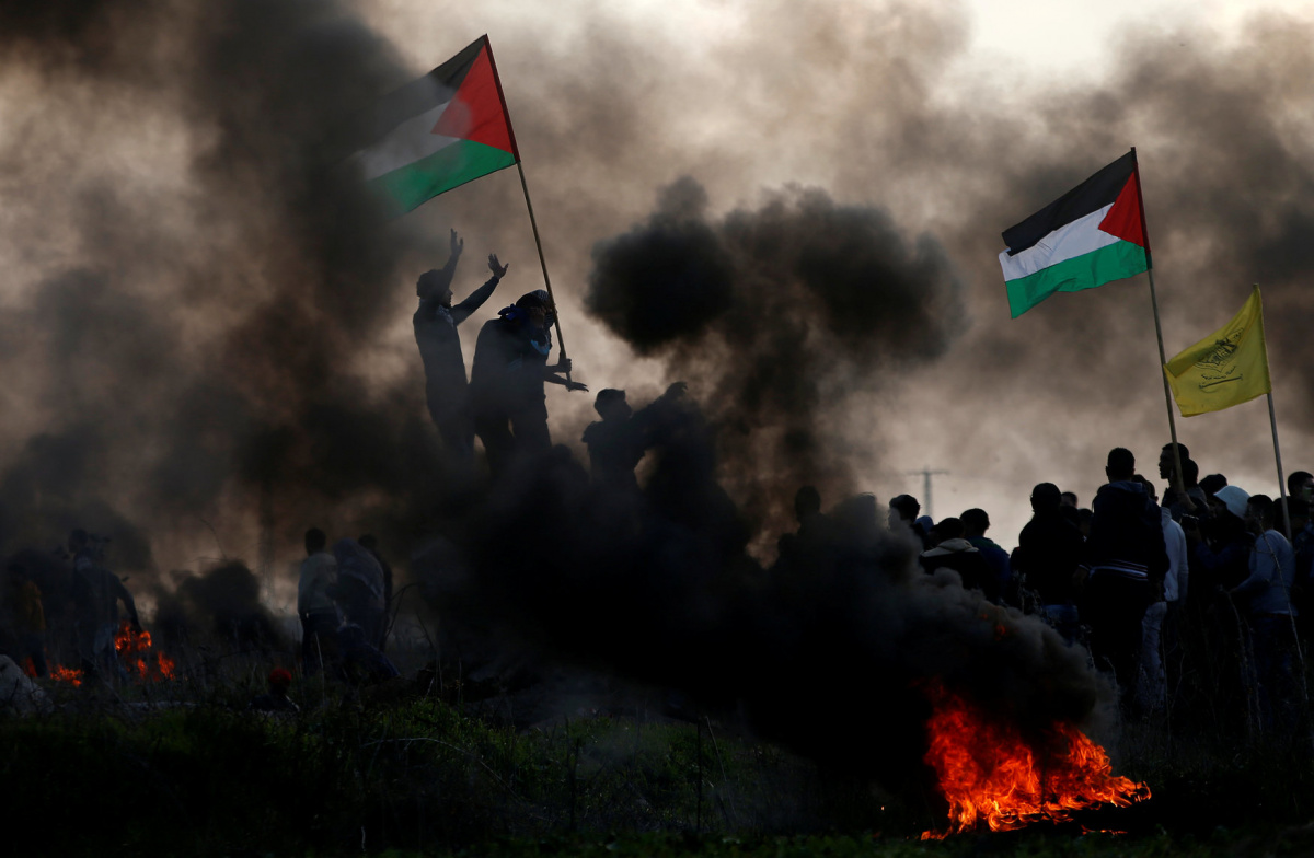 Demonstrators wave Palestinian flags during clashes with Israeli troops, near the border with Israel in the east of Gaza City January 12, 2018. REUTERS/Mohammed Salem