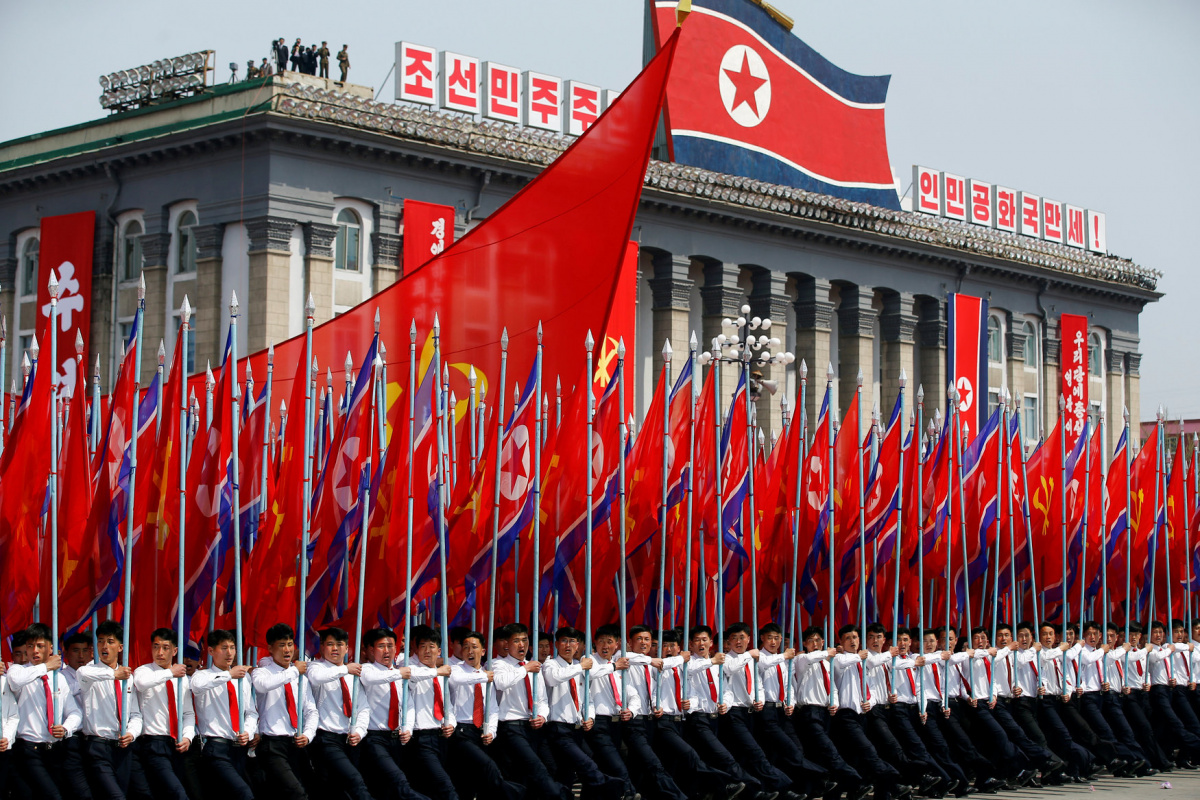 Men carry flags in front of the stand with North Korean leader Kim Jong Un and other high ranking officials during a military parade marking the 105th birth anniversary of the country's founding father, Kim Il Sung, in Pyongyang April 15, 2017. REUTERS/Damir Sagolj/File Photo