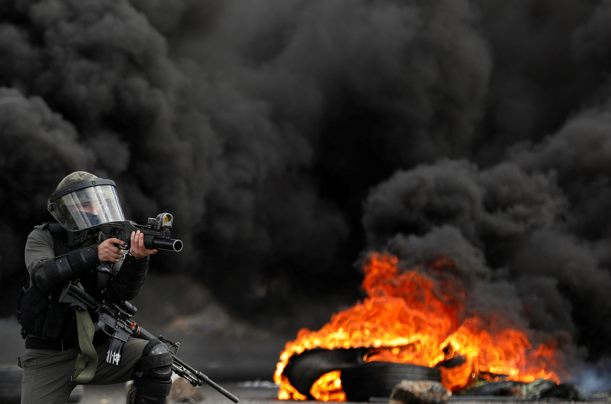 An Israeli border policeman takes up position during clashes with Palestinian demonstrators at a protest against Trump's decision on Jerusalem, near Ramallah, in the occupied West Bank March 9, 2018. REUTERS/Mohamad Torokman