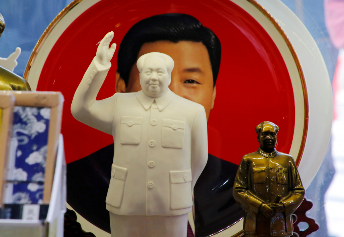 Sculptures of the late Chinese Chairman Mao Zedong are placed in front of a souvenir plate featuring a portrait of Chinese President Xi Jinping at a shop next to Tiananmen Square in Beijing, China, March 1, 2018. To match Analysis CHINA-PARLIAMENT/DISSENT REUTERS/Jason Lee/File Photo