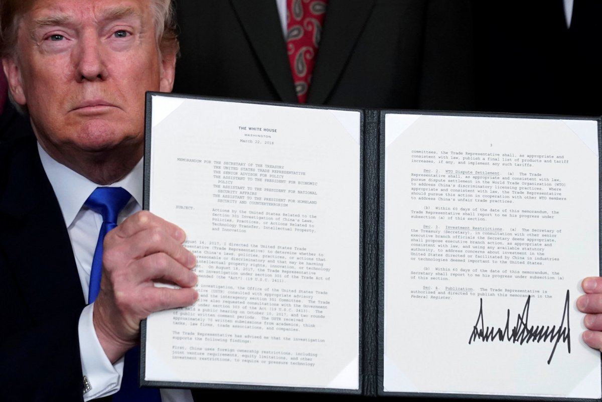 U.S. President Donald Trump holds a signed memorandum on intellectual property tariffs on high-tech goods from China, at the White House in Washington, U.S. March 22, 2018. REUTERS/Jonathan Ernst
