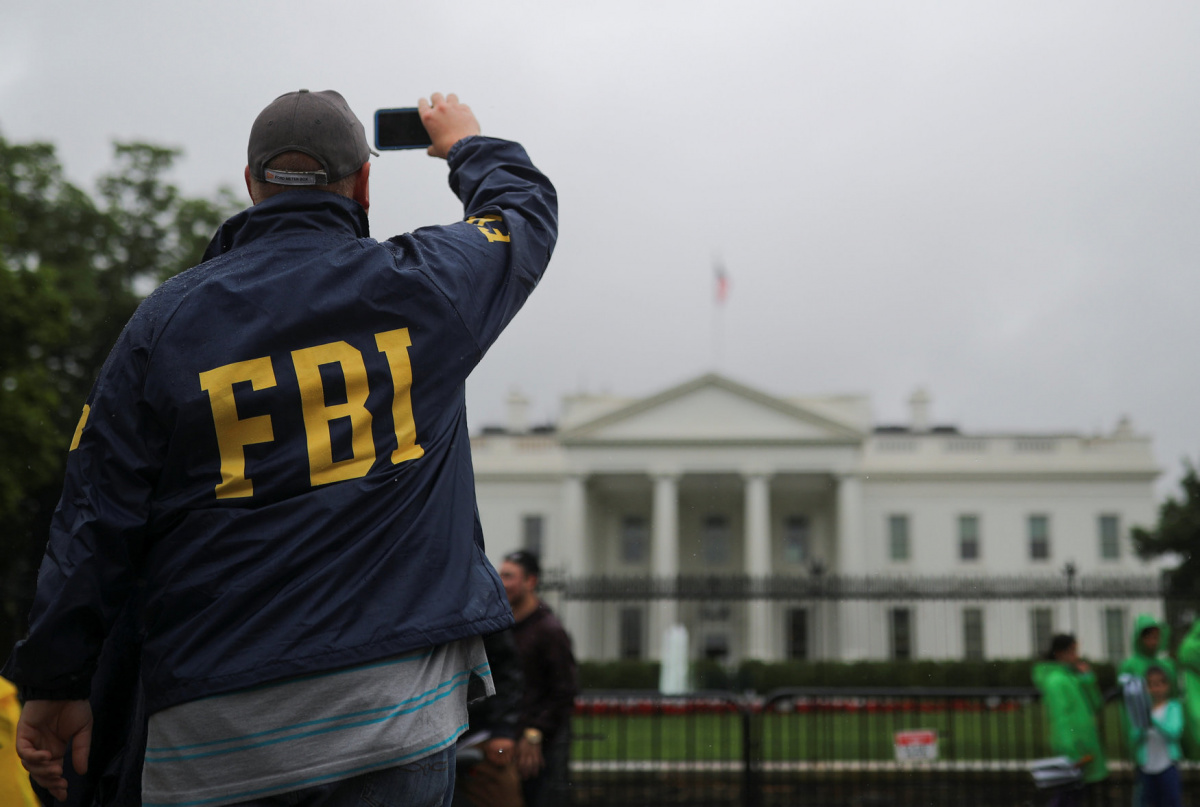 A tourist wearing an FBI jacket stands outside of the White House during a rainy day in Washington, U.S., May 17, 2018. REUTERS/Carlos Barria