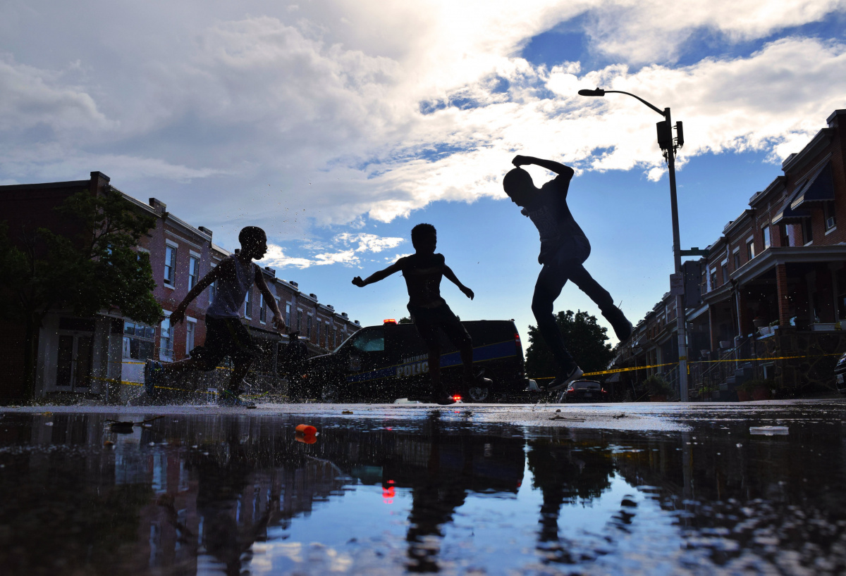 Children play in flash-flood waters as police investigate a July 2 shooting in the 2700 block of E. Chase Street.