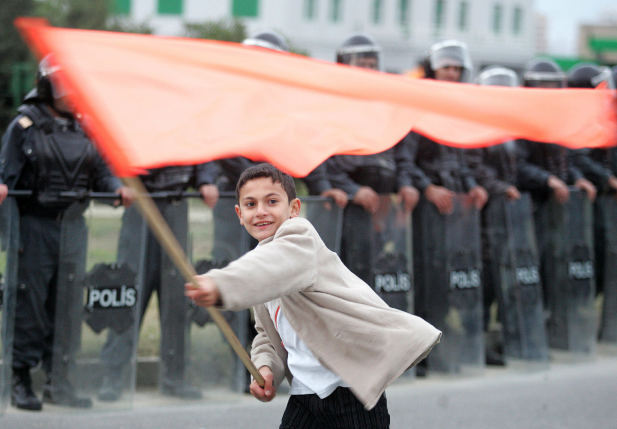 An Azeri boy waves an orange flag in front of a riot police line during an opposition rally in Baku November 9, 2005. Opposition protesters angry about their defeat in Azerbaijan's parliamentary poll massed in Baku on Wednesday, calling on President Ilham Aliyev to step down. REUTERS/Sergei Karpukhin