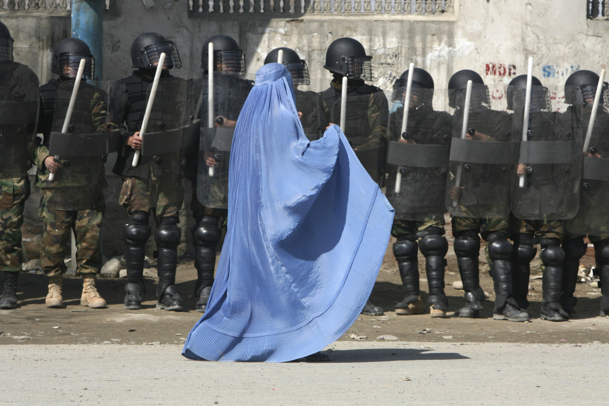 A woman walks past riot police outside a gathering in Kabul's stadium February 23, 2007. Some thirty thousand Afghans staged a gathering in Kabul on Friday to urge President Hamid Karzai to approve a bill that calls for blank amnesty for the country's twenty-five years of war criminals. REUTERS/Ahmad Masood
