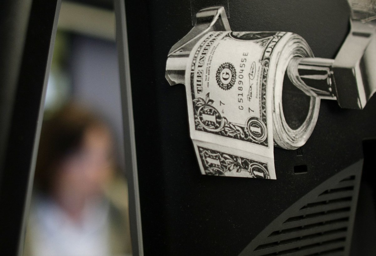 A magazine cut-out of a toilet roll made up of paper money, is taped to a screen of a trading terminal at the German stock exchange in Frankfurt, June 3, 2009. REUTERS/Kai Pfaffenbach