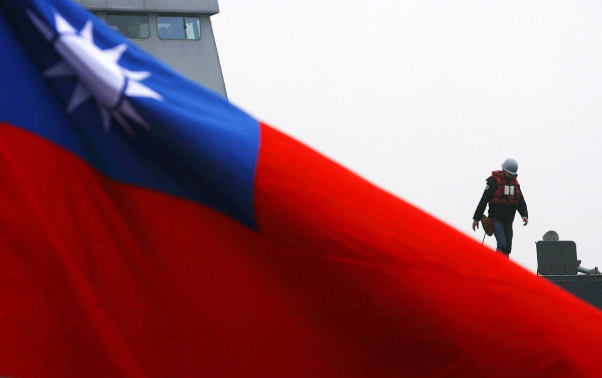 A soldier walks past a Taiwan flag during a navy exercise in Kaohsiung January 26, 2010. The U.S. and China are currently at odds over arms sales to Taiwan, according to local media. REUTERS/Nicky Loh