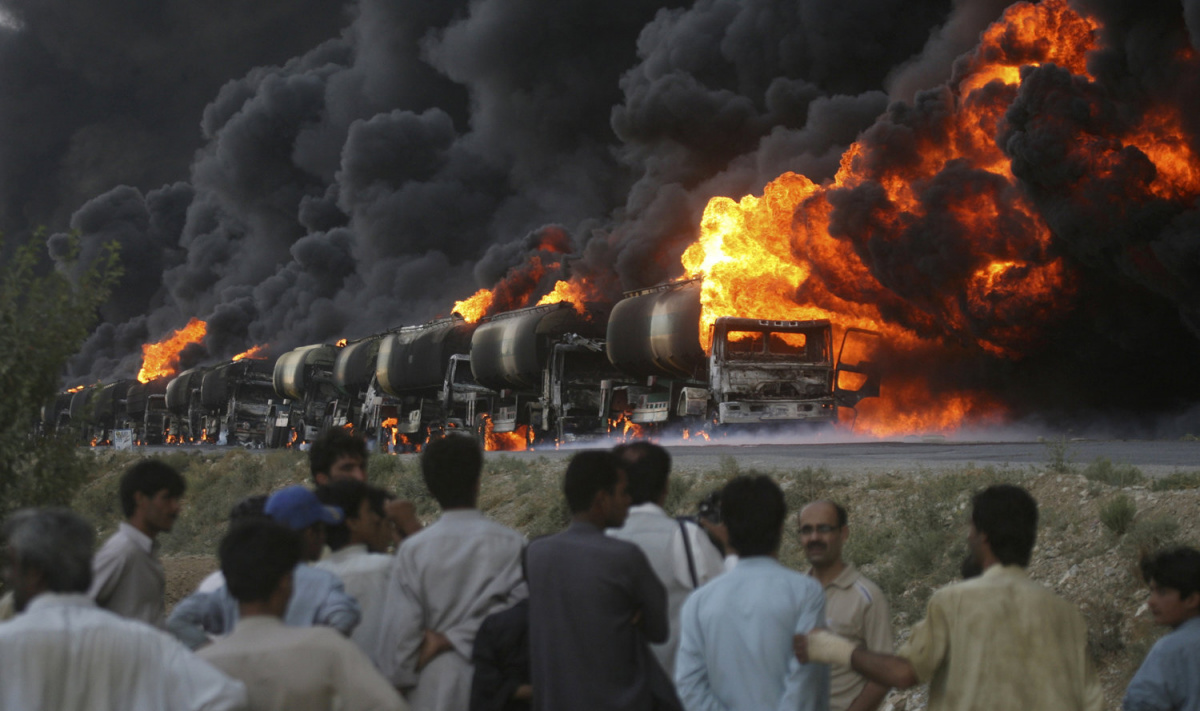 Residents and the media gather near the site of burning tankers, used to carry fuel for NATO forces in Afghanistan, which were attacked by unidentified gunmen on the outskirts of Quetta August 22, 2011. About a dozen gunmen in Pakistan's southwestern district of Mastung attacked and set fire to some 18 trucks carrying fuel for NATO forces in Afghanistan, government and security officials said. There were no reported casualties. REUTERS/Naseer Ahmed
