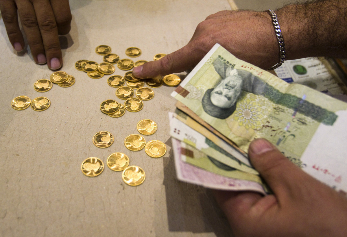 A customer buys Iranian gold coins at a currency exchange office in Tehran's business district October 24, 2011. Iranian media reported last week that monetary authorities had reversed a six-month-old decision to cut interest on bank deposits, aiming to mop up excess cash in the economy and halt a dangerous rise of inflation. The news made sense to economists, who said April's interest rate cut had pushed Iranians to withdraw their savings and rush to buy dollars and gold as a safeguard against inflation --