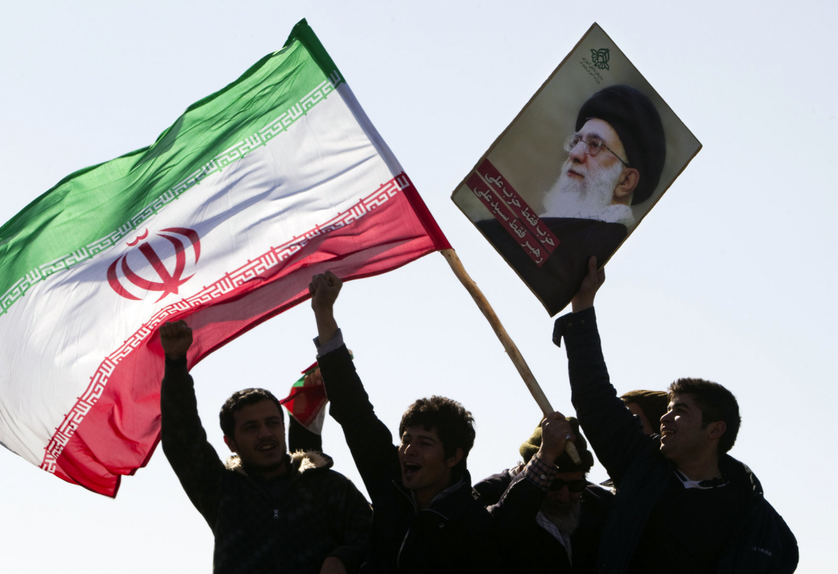 "Demonstrators wave Iran's flag and hold up a picture of supreme leader Ayatollah Ali Khamenei during a ceremony to mark the 33rd anniversary of the Islamic Revolution, in Tehran's Azadi square February 11, 2012. Iran's President Mahmoud Ahmadinejad said on the anniversary of the revolution that the Islamic Republic would soon announce ""very important"" achievements in the nuclear field, state TV reported. REUTERS/Raheb Homavandi"