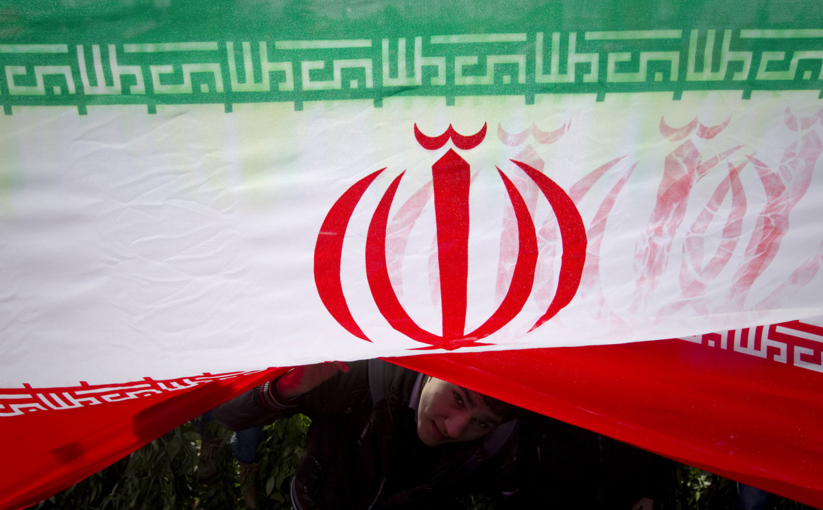 "A demonstrator peeks from under an Iranian flag during a ceremony to mark the 33rd anniversary of the Islamic Revolution, in Tehran's Azadi square February 11, 2012. Iran's President Mahmoud Ahmadinejad said on the anniversary of the revolution that the Islamic Republic would soon announce ""very important"" achievements in the nuclear field, state TV reported. REUTERS/Caren Firouz"