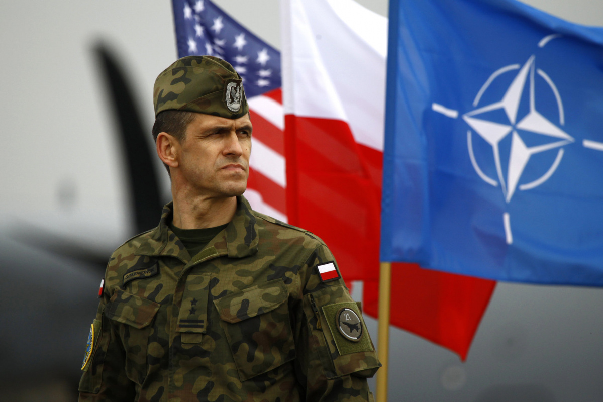 A Polish soldier stands near U.S. and Poland's national flags and a NATO flag as the first company-sized contingent of about 150 U.S. paratroopers from the U.S. Army's 173rd Infantry Brigade Combat Team based in Italy arrived to participate in training exercises with the Polish army in Swidwin, northern west Poland April 23, 2014. The United States is sending about 600 soldiers to Poland and the three Baltic states for infantry exercises, the Pentagon said, one of its highest-profile steps yet to reassure N