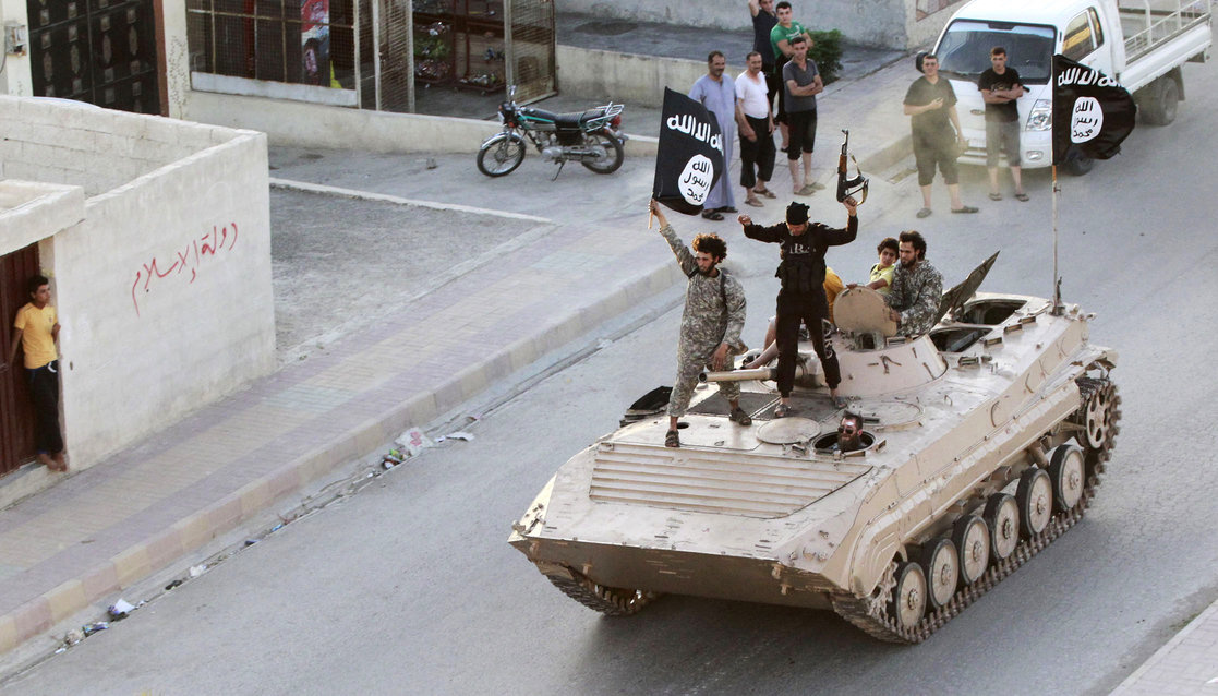 "Militant Islamist fighters take part in a military parade along the streets of northern Raqqa province June 30, 2014. Militant Islamist fighters held a parade in Syria's northern Raqqa province to celebrate their declaration of an Islamic ""caliphate"" after the group captured territory in neighbouring Iraq, a monitoring service said. The Islamic State, an al Qaeda offshoot previously known as Islamic State in Iraq and the Levant (ISIL), posted pictures online on Sunday of people waving black flags from cars"