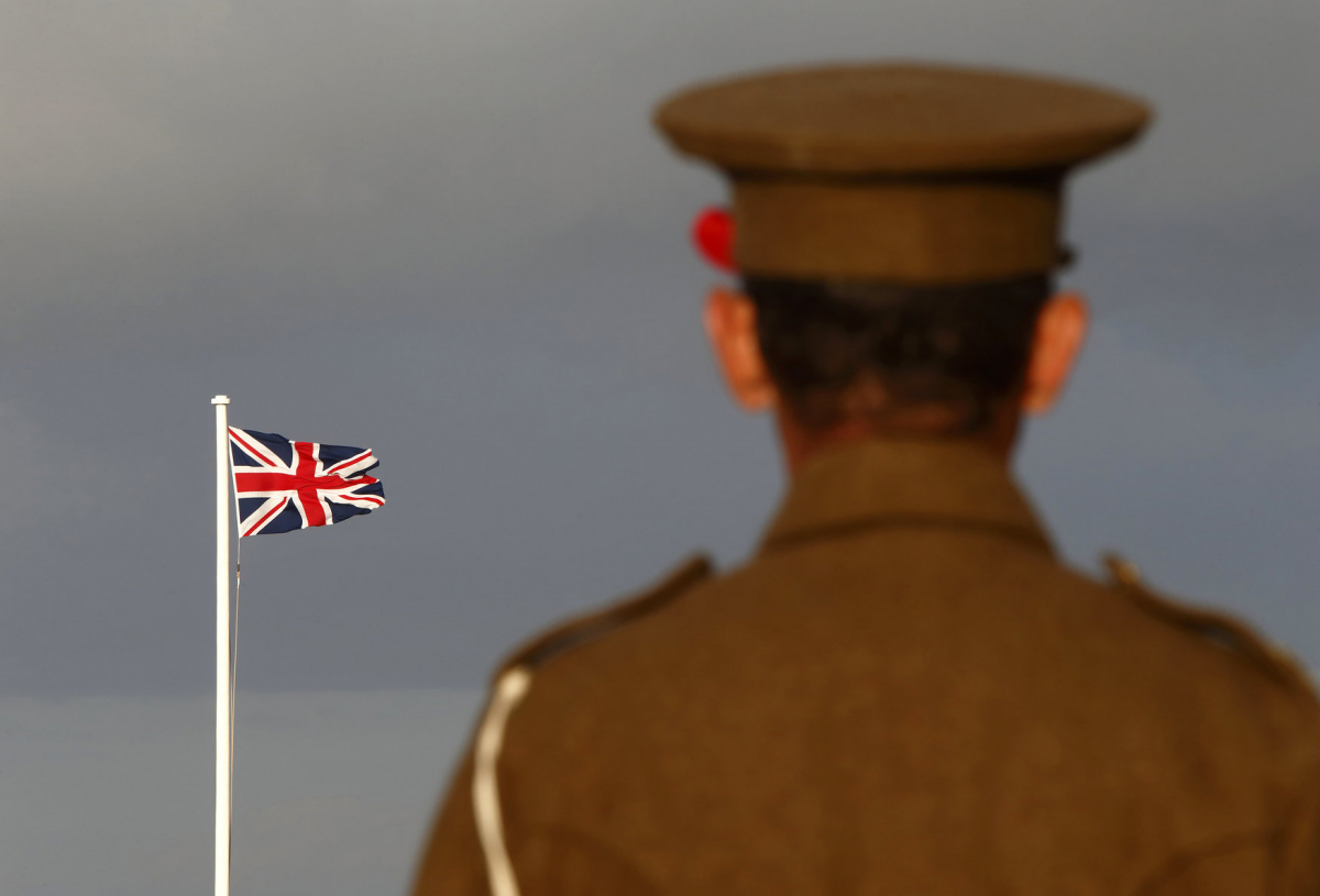A National Heritage Trust historical re-enactor wearing a poppy on his cap looks towards the Union Jack flag while taking part in a re-enactment of British infantry life in the trenches on the Western Front during World War One at the Fort Rinella coastal battery in Kalkara, outside Valletta, November 8, 2014. The event was organised as part of the commemorations of the 100th anniversary of World War One. REUTERS/Darrin Zammit Lupi