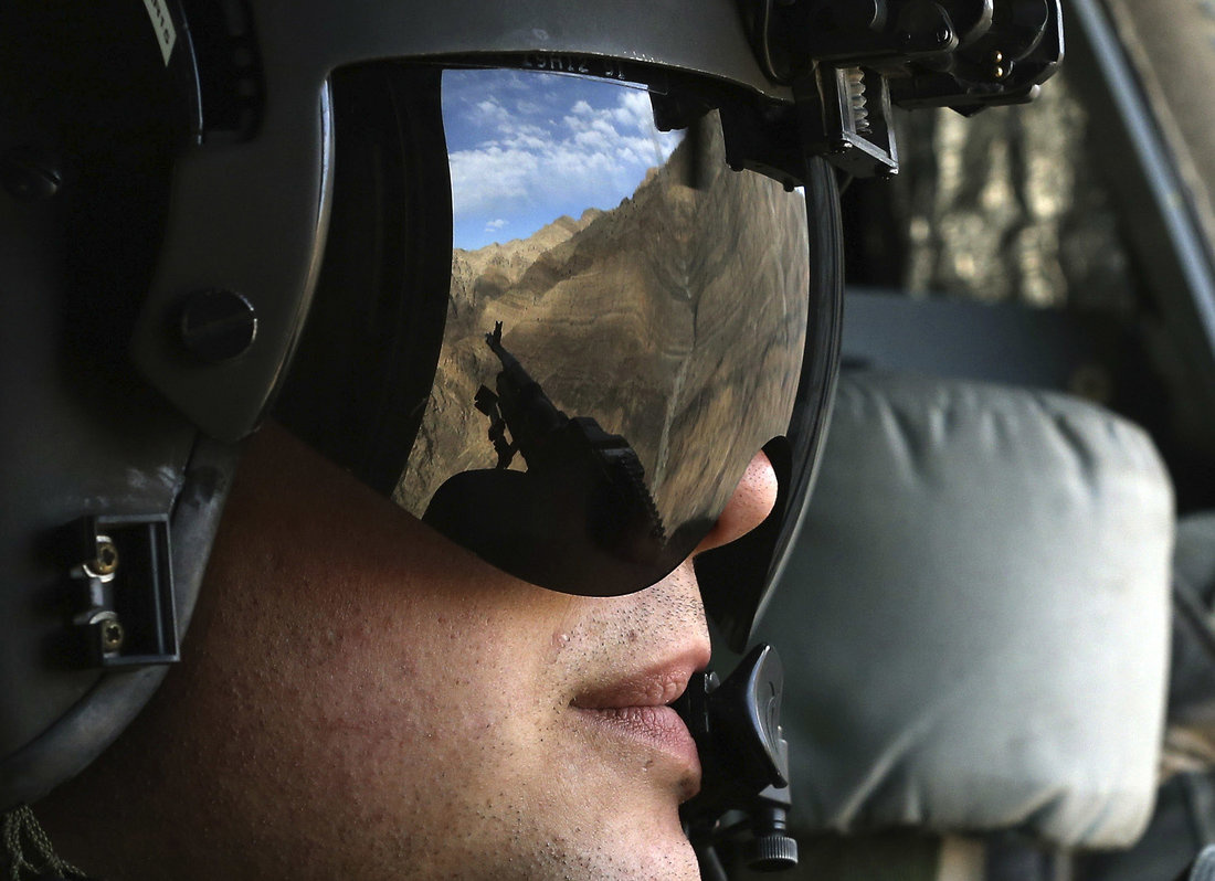 The Afghan mountains are reflected in the visor of a US Army Airborne CH-47 Chinook window gunner while flying behind U.S. Defense Secretary Chuck Hagel as he travels to visit American troops at Forward Operating Base Gamberi December 7, 2014. Hagel on Sunday met with troops in Afghanistan on what is likely his last visit there before stepping down from his post. Hagel's visit comes one day after he announced that the U.S. will keep up to 1,000 more soldiers in Afghanistan into next year than previously pla