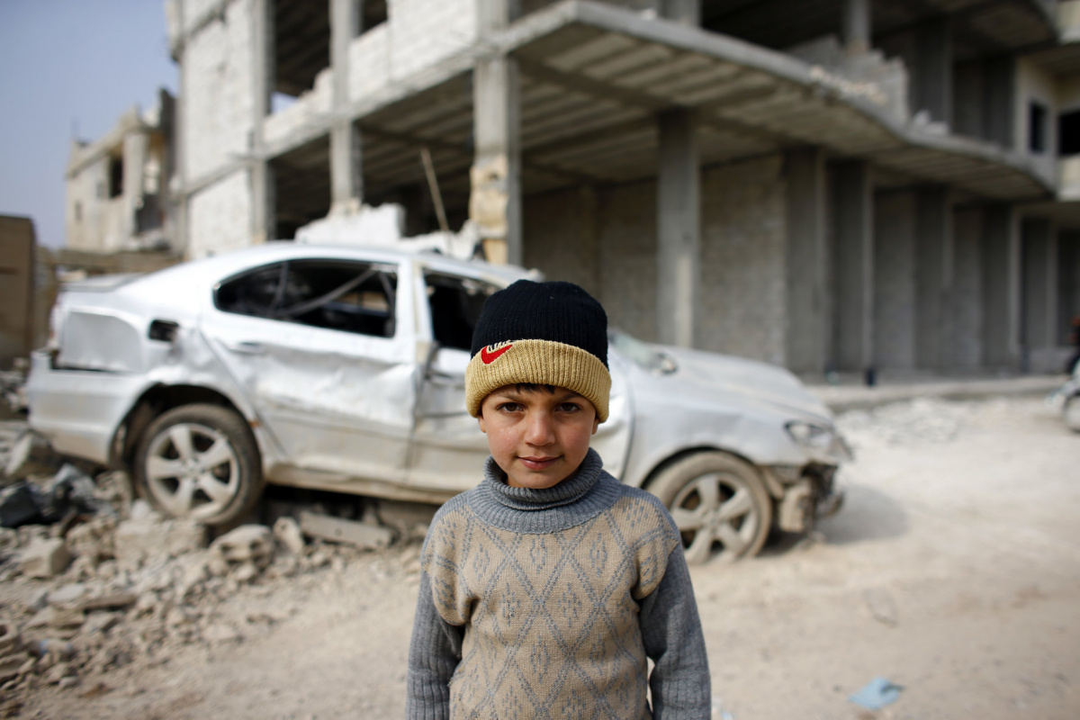 A Kurdish boy stands in front of a damaged car in the northern Syrian town of Kobani January 28, 2015. Kurdish forces battled Islamic State fighters outside Kobani on Tuesday, a monitoring group said, a day after Kurds said they had taken full control of the northern Syrian town following a four-month battle. Known as Ayn al-Arab in Arabic, the mainly Kurdish town close to the Turkish border has become a focal point in the international fight against Islamic State, an al Qaeda offshoot that has spread acros