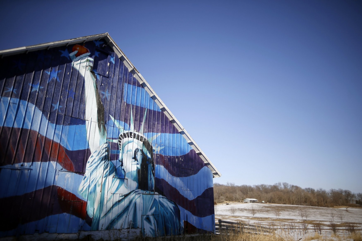 A barn is painted with an image of the Statue of Liberty and a U.S. flag in Mt. Vernon, Iowa, March 8, 2015. Iowa, the American heartland. Endless farm fields and quiet towns. 56,273 square miles that are soon to become the focus of the nation as the long process of electing the next U.S. president begins. REUTERS/Jim Young TPX IMAGES OF THE DAY