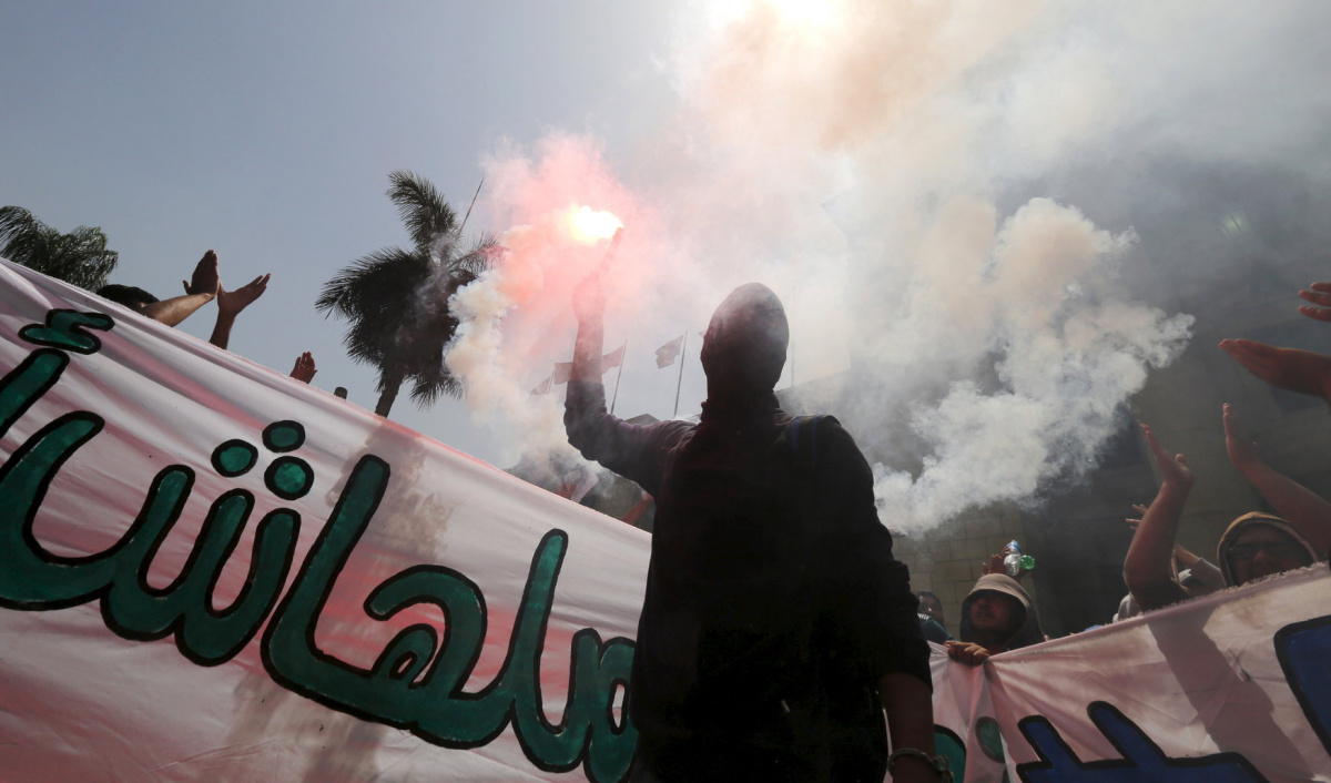 Cairo University students who are supporters of the Muslim Brotherhood and ousted President Mohamed Mursi shout slogans and light a flare during a protest against the military and interior ministry at the university's campus in Giza, on the outskirts of Cairo, April 19, 2015. The protest was organized by students and members of the Muslim Brotherhood in Cairo University ahead of final exams and Tuesday's verdict for ousted president Mursi, according to members of the Muslim Brotherhood. REUTERS/Amr Abdallah