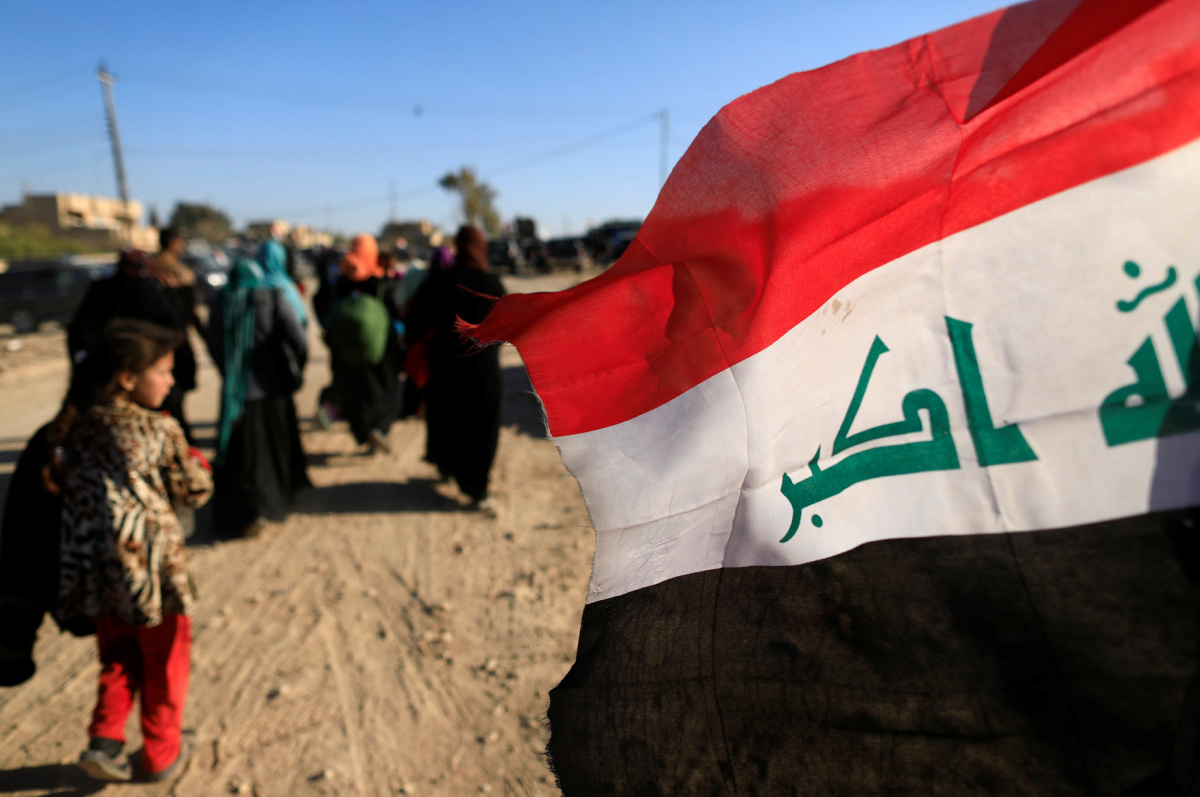 Displaced Iraqis flee their homes during a battle with Islamic State militants walk past Iraqi flag in Albu Saif, south-west Mosul, Iraq, February 25, 2017. REUTERS/Zohra Bensemra