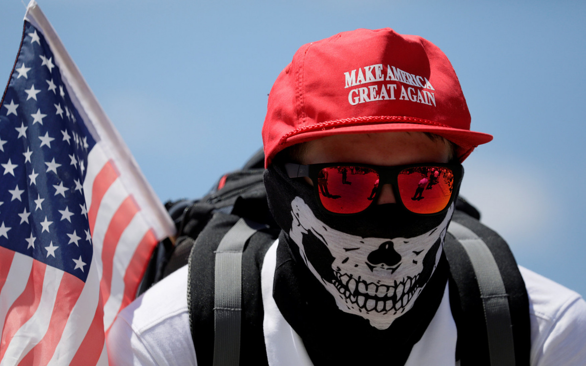 "A masked demonstrator in a Donald Trump ""Make America Great Again"" hat listens to speeches as self proclaimed ""White Nationalists"", white supremacists and ""Alt-Right"" activists gather for what they called a ""Freedom of Speech"" rally at the Lincoln Memorial in Washington, June 25, 2017. REUTERS/Jim Bourg"