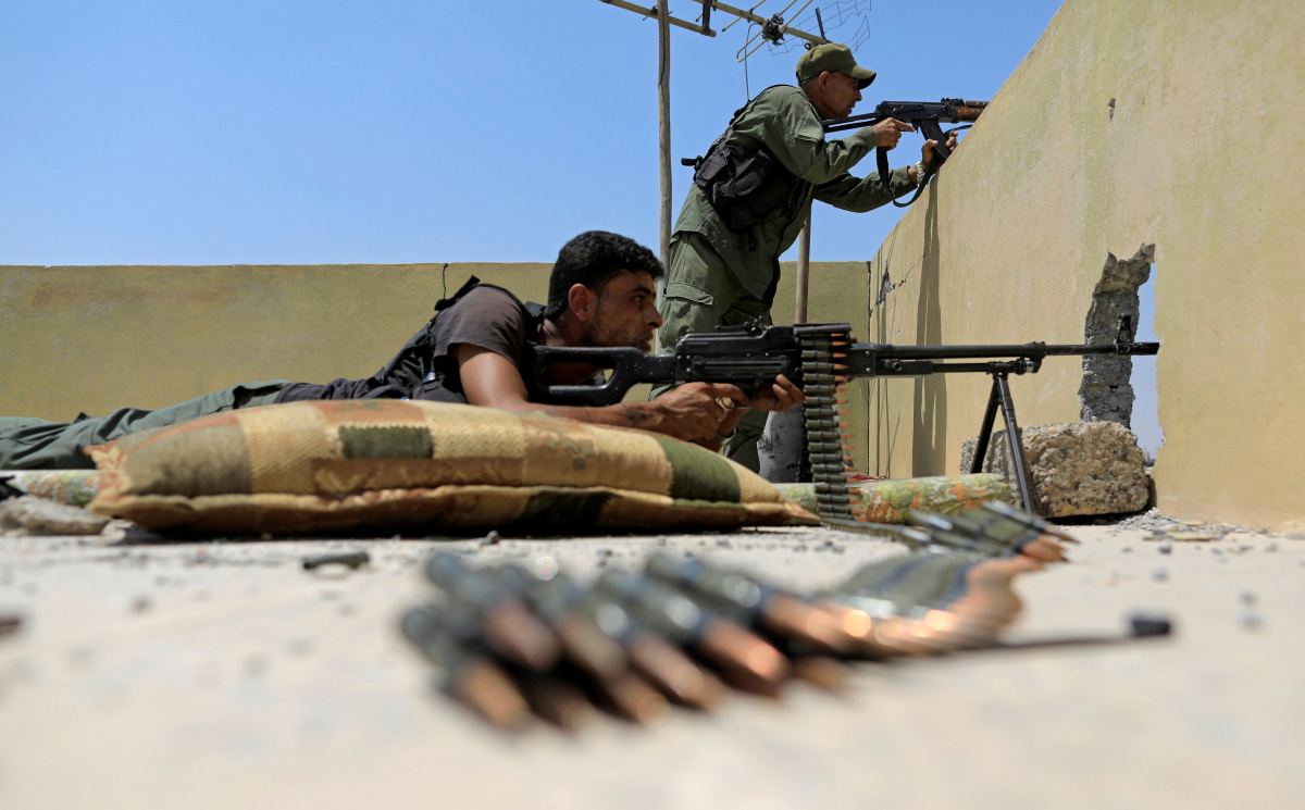 Members of the Syrian Democratic Forces rear guard while their comrade advances toward Islamic State's position in Hisham Bin Abdelmalik, a district of Raqqa, Syria August 13, 2017. REUTERS/Zohra Bensemra