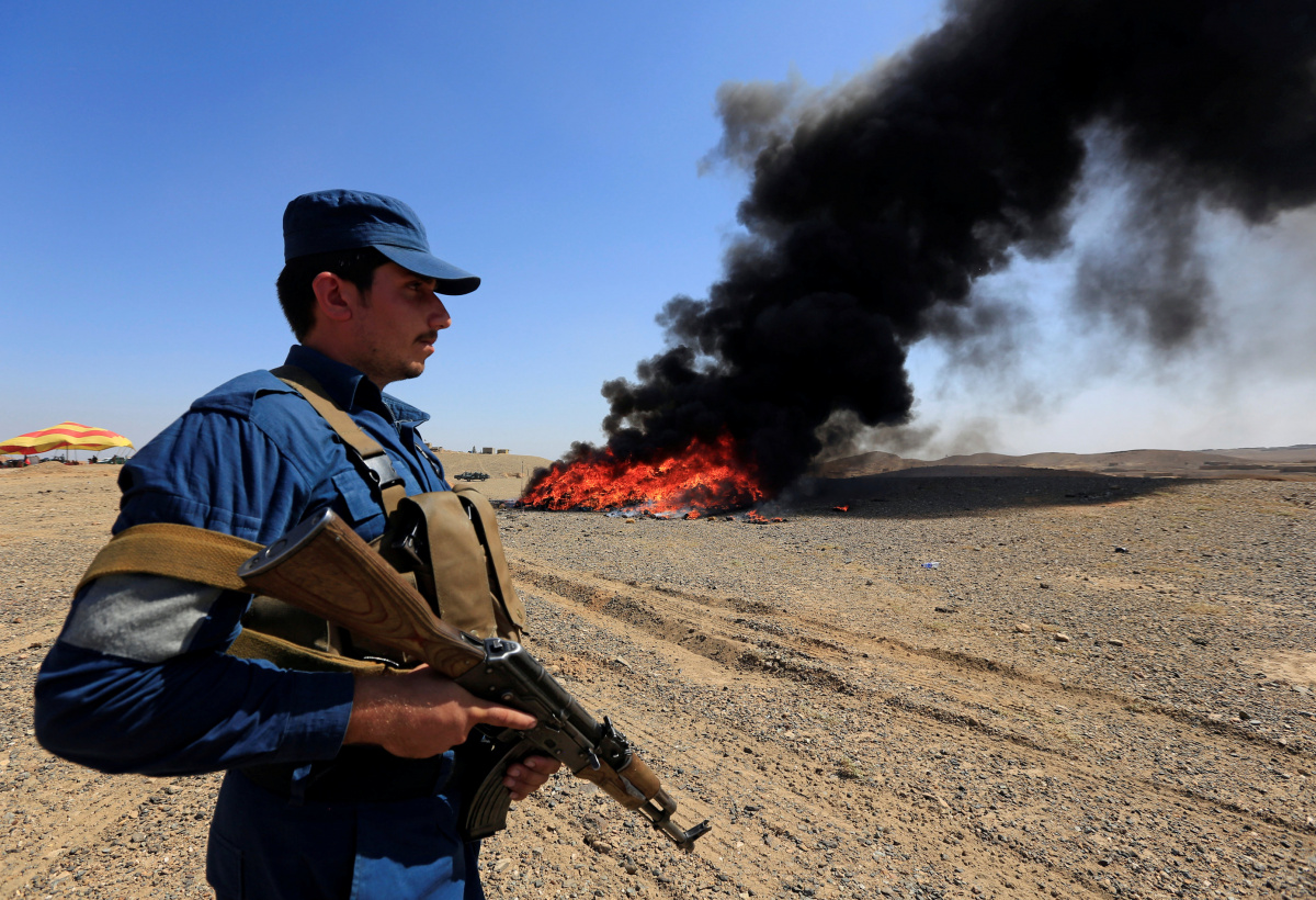 An Afghan policeman stands guard in front of a burning pile of seized narcotics and alcoholic drinks, in the outskirts of Jalalabad, Afghanistan September 26, 2017. REUTERS/Parwiz