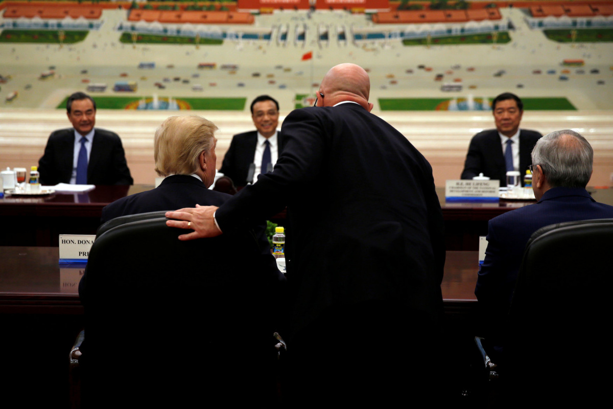 U.S. National Security Adviser H.R. McMaster (standing) speaks with U.S. President Donald Trump as he meets with China's Premier Li Keqiang (C, in background) at the Great Hall of the People in Beijing, China, November 9, 2017. REUTERS/Jonathan Ernst