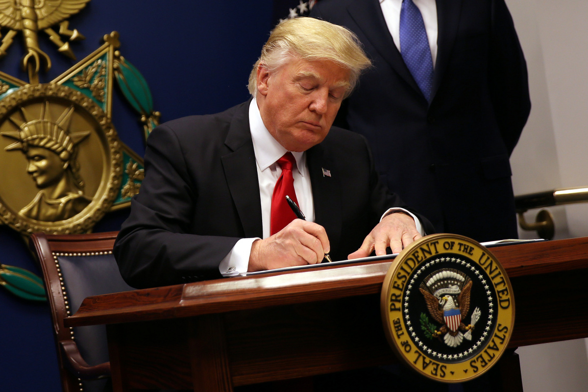 U.S. President Donald Trump signs an executive order to impose tighter vetting of travelers entering the United States, at the Pentagon in Washington, U.S., January 27, 2017. The executive order signed by Trump imposes a four-month travel ban on refugees entering the United States and a 90-day hold on travelers from Syria, Iran and five other Muslim-majority countries. Picture taken January 27, 2017. REUTERS/Carlos Barria