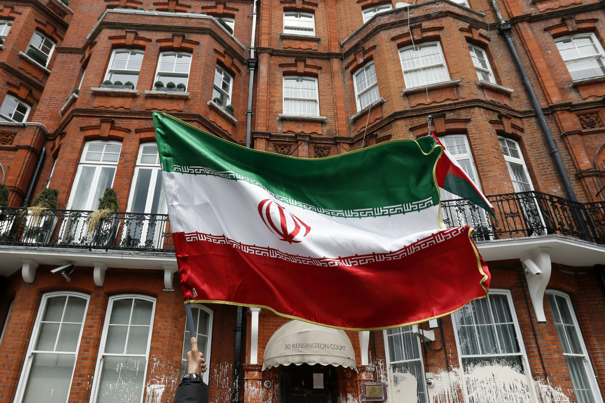 A voter holds a flag outside the Iranian consulate in central London June 14, 2013. The building was the focus for demonstrators, as it was used as a venue for British based Iranians to cast their vote in their country's election to choose a new president. REUTERS/Stefan Wermuth