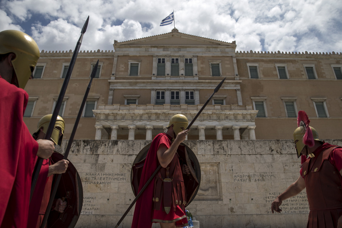 Men dressed as ancient Greek warriors stand in front of the parliament building during a performance in Athens, Greece, June 21, 2015. REUTERS/Marko Djurica