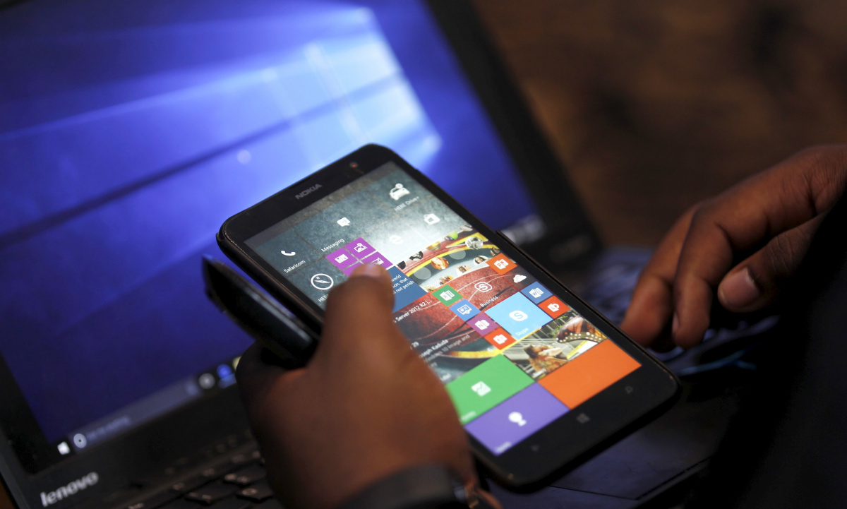 A Microsoft delegate checks applications on a smartphone during the launch of the Windows 10 operating system in Kenya's capital Nairobi, July 29, 2015. Microsoft Corp's launch of its first new operating system in almost three years, designed to work across laptops, desktop and smartphones, won mostly positive reviews for its user-friendly and feature-packed interface. REUTERS/Thomas Mukoya