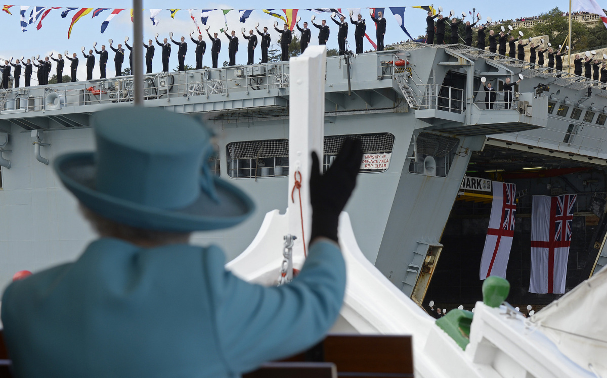 Britain's Queen Elizabeth waves to British Royal Navy crew members performing a salute on the HMS Bulwark amphibious assault ship during a tour of the Grand Harbour in a traditional Maltese fishing boat at the State Visit and Commonwealth Heads of Government Meeting (CHOGM) in Valletta, Malta, November 28, 2015. REUTERS/Toby Melville