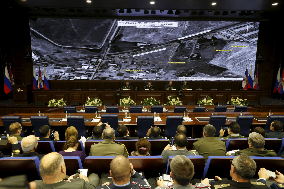 Defence ministry officials sit under screens with satellite images on display during a briefing in Moscow, Russia, December 2, 2015. Russia's defence ministry said on Wednesday it had proof that Turkish President Tayyip Erdogan and his family were benefiting from the illegal smuggling of oil from Islamic State-held territory in Syria and Iraq. REUTERS/Sergei Karpukhin