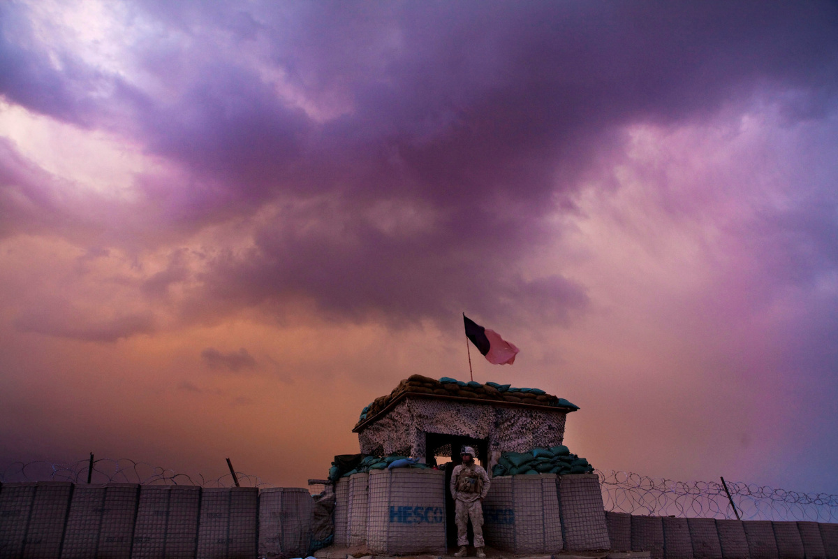 A U.S. Marine from the First Battalion Eighth Marines Alpha Company looks out as an evening storm gathers above an outpost near Kunjak in southern Afghanistan's Helmand province, February 22, 2011. REUTERS/Finbarr
